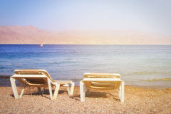 Tropical sea beach and two chaise lounger at sunset light. Summer travel and vacation concept. Photo of tropical sea beach and two chaise lounger at sunset light stock photos