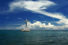 Tropical seascape with cross and clouds. Sunken Cemetery on the exotic island of Camiguin. Seascape and sky with majestic tropical clouds. The cross is a royalty free stock photography