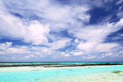 Tropical seascape in Maldives. Tropical seascape of the fresh turquoise sea water, deep blue sky and white clouds in Maldives royalty free stock image