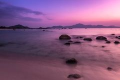 Tropical Seascape with Sandy Beach, Rocks, Mountains and Silky Water before Sunrise stock image