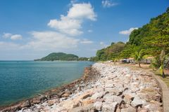 Tropical seascape view of long seashore with green trees and blue sky in the background. royalty free stock image