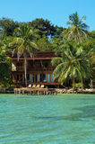 Tropical seaside house with dock and lounger Royalty Free Stock Images