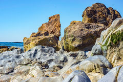 Tropical shore beach with detail of large stones rocks Royalty Free Stock Photos