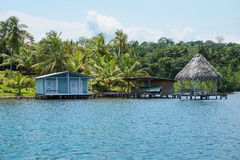 Tropical shore with small house and hut over water Stock Photography