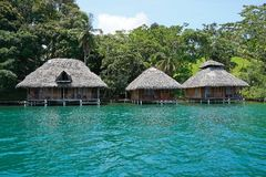 Tropical shore with thatched bungalows over water Stock Photos