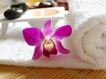 Tropical spa. Aromatic candle, stones, orchid and a white towel Royalty Free Stock Image