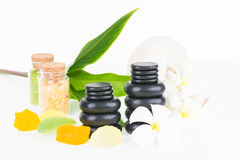 Tropical spa getaway. Spa concept with hot stones, seashell shaped soaps, bath salt, herbal compress ball and flowers on white background Royalty Free Stock Photo