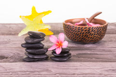 Tropical spa getaway. Plumeria flowers, black stones and starfish shaped soaps on weathered wood close up Stock Photos