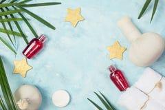 Tropical spa model: witte handdoeken, rode shampooflessen, Thaise masagezakken, gouden sterren en groene varenbladeren op blauwe  Stock Foto's