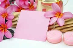 Tropical spa setting white pink paper note on white background. Pink Frangipani on pebble and bamboo mat isoalted on white background stock photo