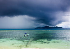 Tropical storm over an island, motor boat Stock Images
