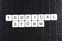 Tropical storm white text word on black cover. Text word crossword. Alphabet letter blocks game texture background. Stock Photography