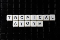 Tropical storm white text word on black cover. Text word crossword. Alphabet letter blocks game texture background. royalty free stock image
