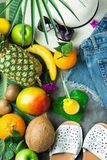 Tropical Summer Fruits Glass of Fresh Juice Pineapple Mango Bananas Coconut on Large Palm Leaf. Women Jeans Shorts Slippers Hat royalty free stock photo