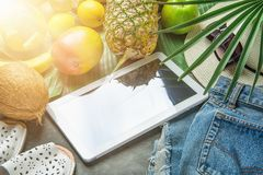 Tropical Summer Fruits Pineapple Mango Bananas Coconut on Large Palm Leaf. Jeans Shorts Slippers Hat Sunglasses Tablet. Arrangement Composition with Tropical Royalty Free Stock Image