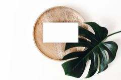 Tropical summer stationery mock-up scene. Blank business card, wooden tray, green monstera leaf isolated on white table stock photo