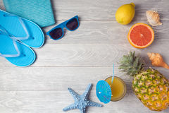 Tropical summer vacation background with pineapple, juice and flip flops on wooden table. View from above. stock image