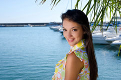 Tropical summer vacation. Beautiful girl smiling standing under a palm tree. Royalty Free Stock Photo