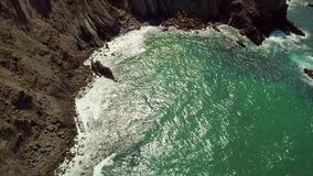 Tropical sun shining in ocean. Aerial view from drone of tropical sunlight reflecting in turquoise water of ocean washing rocky shoreline of Algarve, Portugal stock footage