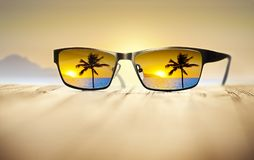 Tropical Sunglasses Travel Vacation Palm Tree. A tropical sunset as seen through sunglasses with a tropical island in the background Royalty Free Stock Photography
