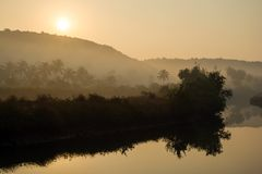 Tropical sunrise over river. Tropical sunrise over misty river Royalty Free Stock Photo