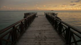 Tropical sunrise over wooden jetty pier on caribbean sea stock footage