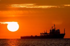 Tropical sunrise or sunset at sea. Calm ocean image of a ship on. The horizon. Travel destination and tourism scene Stock Image