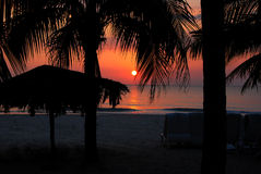 Tropical Sunset. Sunset on beach in tropical resort with palapa and beach chairs Stock Image