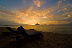 Tropical sunset. Two beach chairs can be seen in the foreground Royalty Free Stock Photography