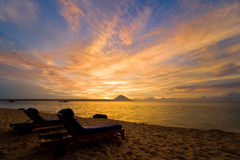 Tropical sunset. Two beach chairs can be seen in the foreground Royalty Free Stock Photos