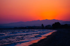 Tropical sunset on the beach with mountain. Stock Photography