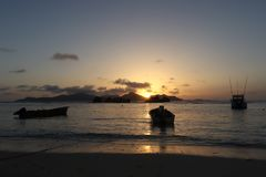 Tropical sunset at beach. Anchored boats in the ocean and the Island of Praslin stock photos