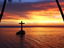Tropical Sunset with Cross Silhouette. Sunset at Sunken (underwater) Cemetery memorial, Camiguin Island (Mindanao, Philippines): colorful tropical sky after a Royalty Free Stock Photos