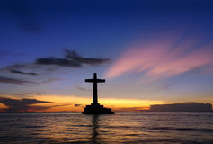 Tropical sunset with cross silhouette. royalty free stock images
