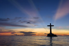 Tropical sunset with cross silhouette. stock photo