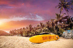 Tropical sunset at Goa beach. Yellow surf board at paradise tropical beach with purple cloudy sunset in Goa, India Stock Photos