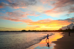 Sunset in the tropics on the ocean coast. The child is jumping on the beach. Bright colors of sky are reflected in water and sand Stock Images