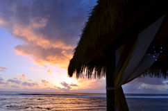 Tropical sunset over a beach bungalow Stock Image