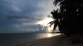 Tropical sunset over a cloudy sky. Footage showing the last minutes of a tropical sunset, over the ocean and white sand beach. It is a cloudy afternoon and calm stock footage