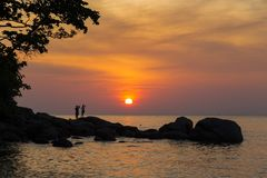 Tropical sunset over the ocean. Evening on the ocean coast.  Phu. Orange - red tropical sunset over the ocean. The sun sits in the clouds. Stones on the shore Stock Photography