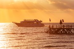 Tropical sunset. Sunset with palm leaves boat and pier Royalty Free Stock Image
