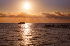Tropical sunset. Sunset with palm leaves boat and pier Stock Photography