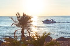 Tropical sunset. Sunset with palm leaves boat and shore Stock Photography