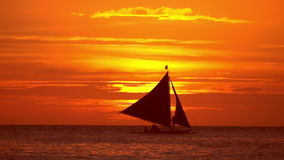 Tropical sunset. Sail boats silhouettes on ocean horizon. Boracay, Philippines