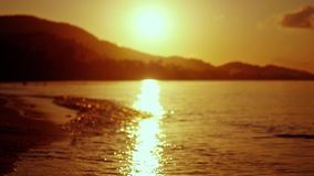 Amazing tropical golden sunset in the sea in slow motion with bokeh lights. 1920x1080. Tropical sunset in the sea stock video footage