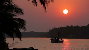 Tropical sunset seascape with a boat. And palm trees stock video