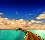 Tropical sunset seascape. overwater bungalow with jetty Stock Photography