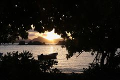 Tropical sunset seen through leaves. Anchored boat in the ocean and the Island of Praslin stock image
