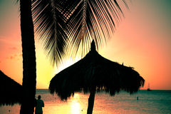 Tropical Sunset. With silhouetted palapa grass hut and palm trees and man Royalty Free Stock Photo