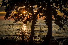 Sunset with sunbeams and silhouette of swing at the beach royalty free stock image